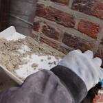 Artisan faisant joints façade briques.