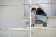 Artisan réalisant crépi façade.