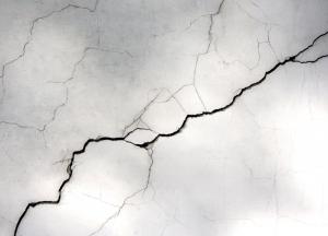 Appliquer un traitement pour la réparation des fissures d'une façade.